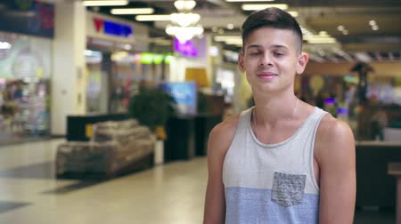 cheerfulness : Optimistic view of a handsome young brunet man in a sleeveless singlet standing and smiling happily in a big supermarket in Ukraine in summer.