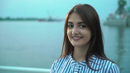 dişlek : Cheerful view of a pretty young brunett woman in striped dress smiling happily leaning on the quay fence with blue waters in the background