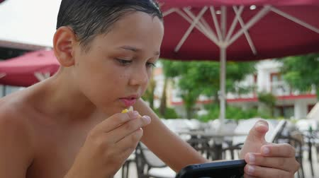 parasol : Exciting view of an optimistic small boy in shorts eating lemon in a sea resort cafeteria in slow motion. He looks happy and optimistic.