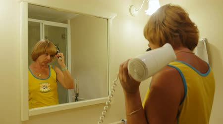bob hairstyle : Profile of a fashionable blond woman taking care of her bob hairstyle with a fan and a round brush being dressed in a yellow T-shirt