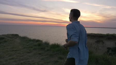 otimismo : Impressive view of an athletic young brunet man in a shirt and pants jogging on a sea coast  at splendid sunset in summer in slow motion