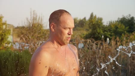 peppy : Optimistic view of a jolly man having a hydromassage from a stream of water outdoors on a  lake bank on a sunny day in summer in slow motion. Stock Footage