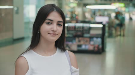 arejado : Cheery portrait of of a happy young woman in a white dress with long loose hair putting it in order and laughing in a big mall in summer