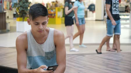 jovial : Cheerful view of a young brunet man with a short haircut in a singlet and shorts sitting and browsing the internet on his smartphone in a mall