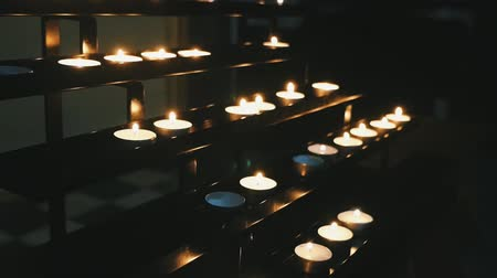 especially : Striking view of several rows of catholic candles lit in a cathedral being placed on a staircase looking shelves and reminding about eternity