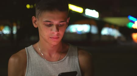 surfing the net : Portrait of a young brunet guy with short haircut in a grey tank-top browsing the net on his smartphone in a city street at night in summer