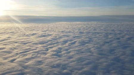 romênia : Fantastic bird`s eye view of white clouds flying down like high peaks at shining sunset with shimmering rays rom an airplane window in summer