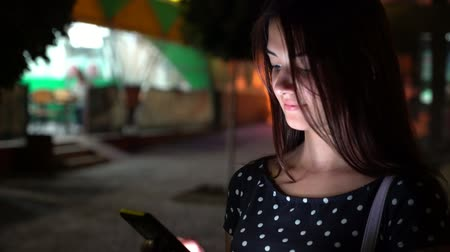 ищу : Bokeh view of a thoughtful brunette girl in a fashionable spotted dress seeking info on her smartphone in a lit city street at night in summer