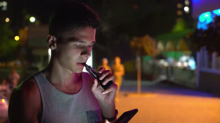 vaper : Bokeh view of snappy young man in  sleeveless shirt smoking electronic cigarette and browsing the net on his smartphone in city at night in summer