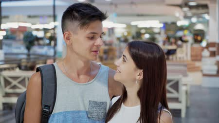 gevşemiş : Romantic view of an attractive young woman with elegant long hair talking and smiling with her sportive boyfriend  in a striped A-shirt in a mall Stok Video