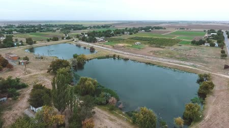 straight road : Breathtaking bird`s eye view of two small square lakes with a white administrative house and a highway running nearby in Kherson region in summer