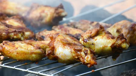 grillowanie : Chicken wings and legs cooking on a barbecue grill, closeup. Outdoor cooking.
