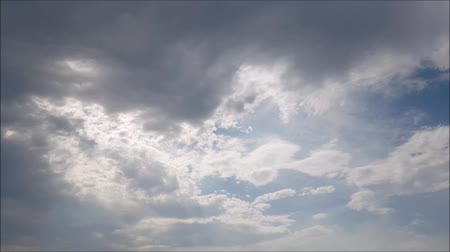 şartlar : Blue sky with white, gray and black clouds. The Sun between clouds. Stok Video