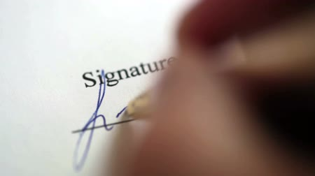 assinatura : Close-up of a  hand writing a signature on the document