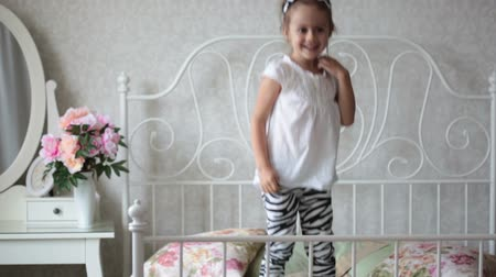 капелька : Little girl is jumping on the bed