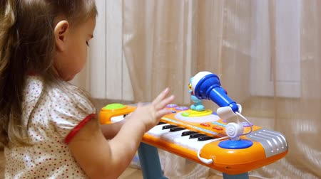 tehetség : Child little girl playing on a toy piano