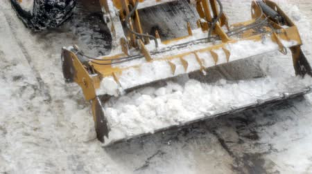 wheel loader : A tractor clears snow from a road