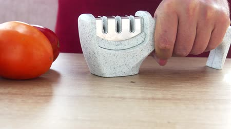 bilenmiş : Manual sharpening of a knife in a special sharpener Stok Video