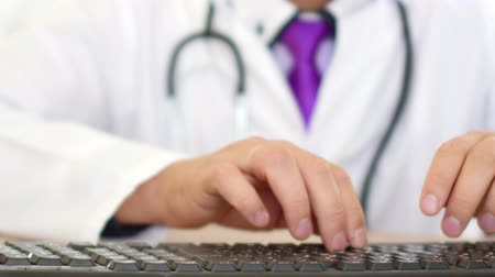 cabinet : Male doctor hands typing prescription on computer keyboard