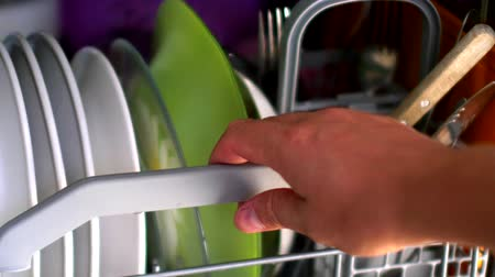 kitchenware : Man taking out dishes from the dishwasher