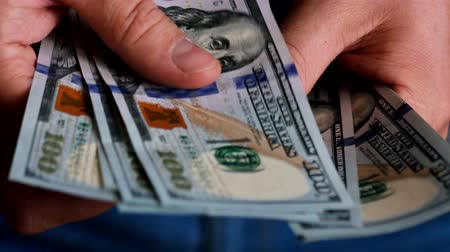 ganancioso : A businessmans hands counting hundred dollar bills Vídeos