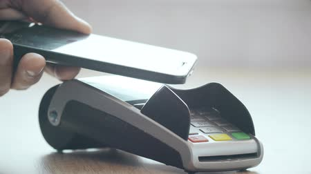 caixa : Customer paying with NFC technology by mobile phone on POS terminal Vídeos