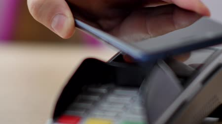 caixa : Person using contactless payment with smartphone.