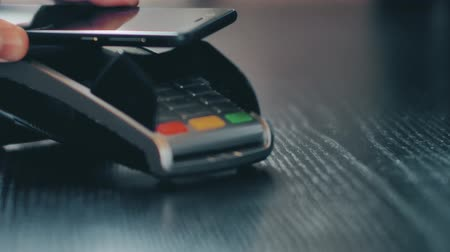 nfc : Hand with a smart phone using the terminal for payment by NFC technology Stock Footage