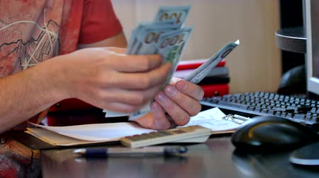 benefício : Man counting money and filling tax form