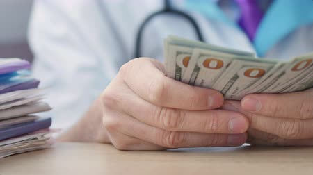 łapówka : Corrupted medical doctor counting money.