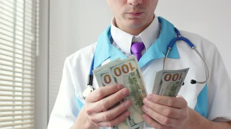 corruptible : Male medical doctor counting hundred dollars banknotes