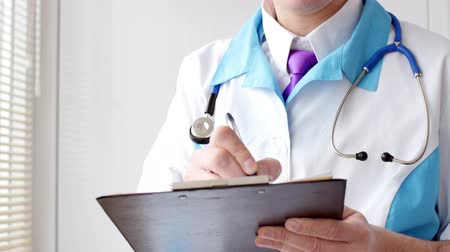 vágólapra : A doctor filling up medical form on a clipboard.