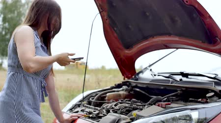 Young woman having trouble with her broken car.