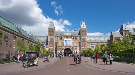 Amsterdam, Netherlands - May 13, 2019: People in Amsterdam city with Rijksmuseum in Background a Dutch national museum in Amsterdam city, Netherlands