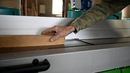 Processing wood with electrical plane in workshop