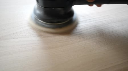 Man sanding wood with orbital sander in a workshop Стоковые видеозаписи