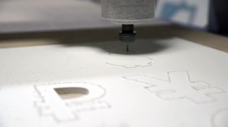 řezačka : Milling cutting machine makes a plotter cutting in plastic currency DOLLAR signs