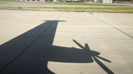 ar : Shadow on runway strip commercial screw aircraft. View from window.