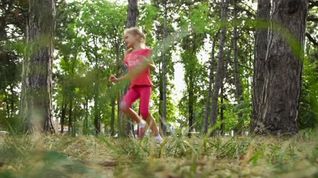hét : Girl running in the park among the trees. Defocused shooting.