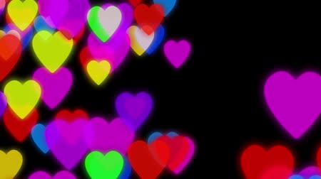 zaoblený : Hearts background animation. Colorful hearts slowly falling down on a dark background with particles flowing around Dostupné videozáznamy