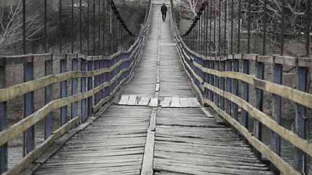 подвесной : Man is walking along on a rope suspension bridge