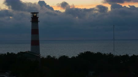 Timelapse sunset with lighthouse on the sea under stormy clouds in the background