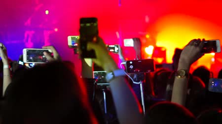 Making party at a rock concert and hold smartphone cameras with digital displays