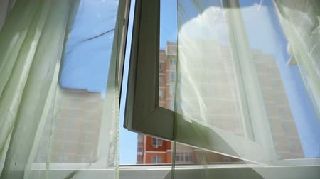 Window with curtains and a view of the sky and city. Conceptual story of the room and open Windows.