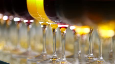 Glasses with alcohol and different drinks, glasses of wine and juice are on the buffet table in a restaurant, red wine in glasses.