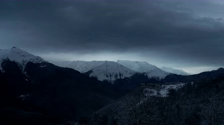 Timelapse of dramatic sky in the winter mountains landscape. Clouds and shadows. Houses in the mountains Wideo
