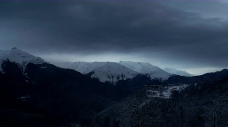 Timelapse of dramatic sky in the winter mountains landscape. Clouds and shadows. Houses in the mountains.