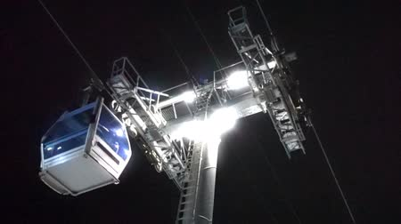 Cable car lift at ski resort. Night skiing from the mountains.