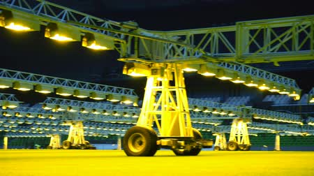 Mobile grow lighting system in sports stadium at night. Wideo
