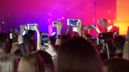 Crowd making party at rock concert and hands hold many cameras with digital displays among people